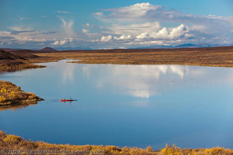 Canoers paddle on a calm lake in the Alaska Range mountains, along the Denali highway, Interior, Alaska.