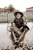VIETNAM, Hue, portrait of Nguyen Thi Ngan in her small canoe sitting with her hand paddles and a pile of leafy green vegetables called rau muong, outside the Citadel in the Citadel canal (B&W)