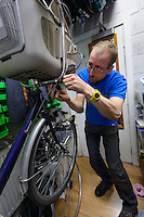 "Noah Fisher, owner of Mamachari Bikes, working on a bike. Dalston, London, UK, March 29, 2014.  Mamachari sells Japanese ""mamachari"" shopping bikes in the East End of London."