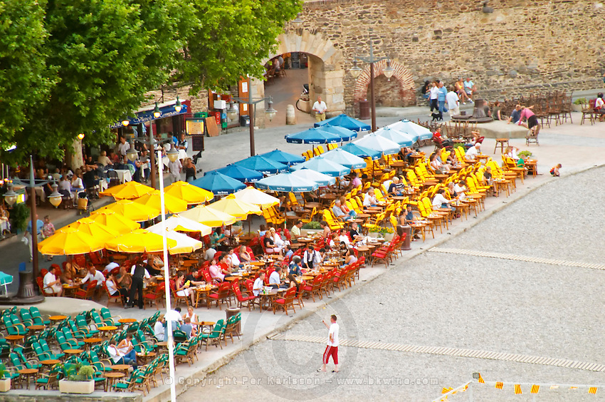 Cafes on the beach with colourful sun shade umbrellas. The beach in the village. Collioure. Roussillon. France. Europe.