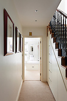A traditional style staircase with a cupboard built under the stairs to provide extra storage.