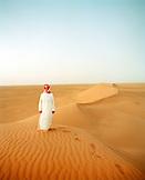 SAUDI ARABIA,The Empty Quarter, Najran, teenage boy standing on sand dune