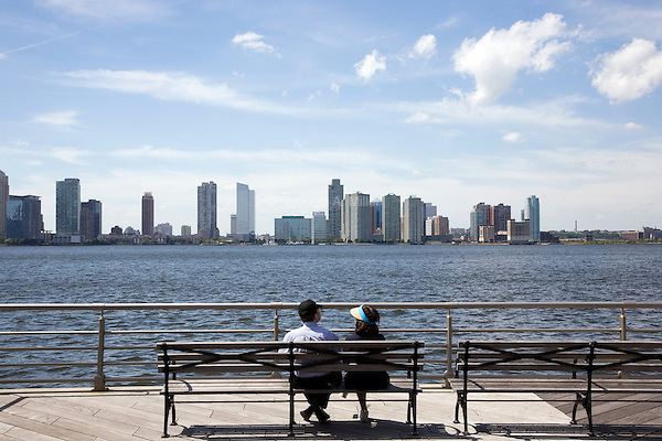 A couple sit on a bench and take in the view of Hoboken, New Jersey from Hudson River Park along the West Side Highway in New York City, New York on 24 August 2011.