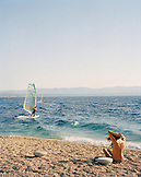 CROATIA, Bol, Brac, Dalmatian Coast, sunbather and windsurfer in Zlatni Rat Beach.