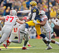 Ohio State Buckeyes defensive lineman Adolphus Washington (92) and linebacker Darron Lee (43) hit Michigan Wolverines quarterback Jake Rudock (15) after a pass in the 2nd quarter at Michigan Stadium in Arbor, Michigan on November 28, 2015.  (Dispatch photo by Kyle Robertson)