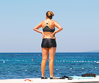 Young shapely woman standing on a jetty clad in a black bikini with hotpants hot pants type bottom, hands on hips looking out over the sea. Uvala Sumartin bay between Babin Kuk and Lapad peninsulas. Dubrovnik, new city. Dalmatian Coast, Croatia, Europe.