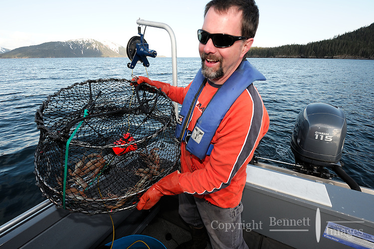 Dug Huntman shows off his catch after pulling a shrimp pot in Passage Canal near Decision Point, Prince William Sound, Southcentral Alaska on a sunny spring afternoon in early May. MR