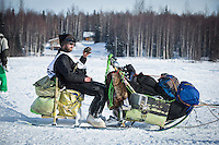 Nicholas Petit sits on his sled and sips coffee as he travels down long Lake after leaving the restart of the Iditarod sled dog race in Willow, Alaska at Sunday, March 3, 2013.