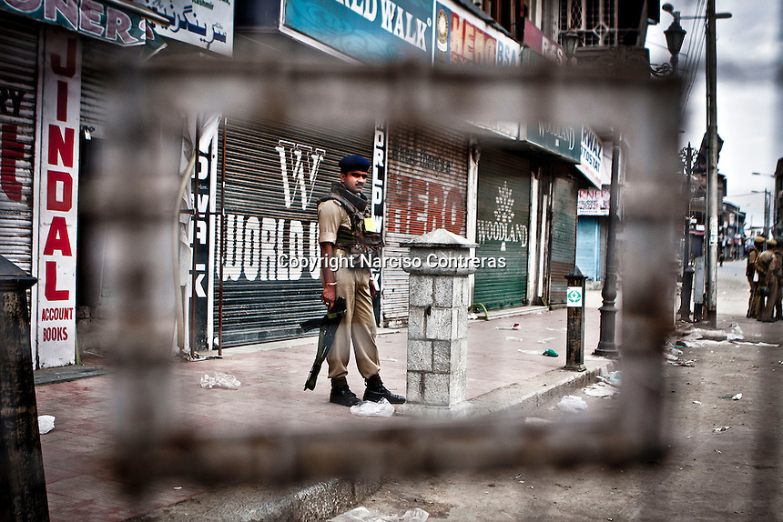 Indian paramilitary soldier stands guard at a check point in Lal Chow area, Srinagar, as India is celebrating the Independence day. The curfew was declared into the most conflictive areas across the city and districts into the Kashmir valley. Security has been beefed up by indian paramilitary forces (CRPF), army and police on streets and check points.