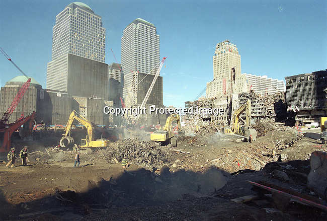 "Smoke rises from the earth as heavy machinery excavates debris from ""ground zero"" November 9, 2001 in New York City. It is estimated that it will take a year to clear the debris from the site of the World Trade Center terror attacks. .Photo: Per-Anders Pettersson/iAfrika Photos"