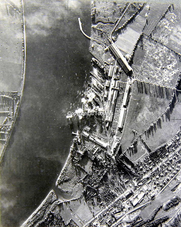 BNPS.co.uk (01202 558833)<br /> Pic:  Tooveys/BNPS<br /> <br /> Taken on 12/08/41 - The results of a bombing raid on the shipyard at Le Trait, North West France. <br /> <br /> Dramatic photos showing a series of heart-pounding World War Two bombing raids from the pilot's perspective have come to light.<br /> <br /> They were taken from Blenheim bombers undertaking attacks on targets in Germany and Nazi-occupied Netherlands in 1941.<br /> <br /> Several capture the immediate aftermath of a direct hit, with flames and clouds of smoke signifying they had achieved their aim.<br /> <br /> The album, which contains almost 100 photos, has emerged for sale with Toovey's Auctions, of Washington, west Sussex.