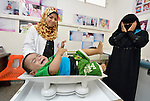 As the worried mother looks on, nurse Asma El Shami weighs a child in the pediatric department of the Al Ahli Arab Hospital in Gaza City. The Anglican Church-affiliated hospital is a member of the ACT Alliance.<br /> <br /> The 2014 war provoked serious damage to Gaza's health infrastructure. Seventeen hospitals, 56 primary health care facilities and 45 ambulances were damaged or destroyed. Sixteen health care workers were killed and 83, most of them ambulance drivers and volunteers, were injured.