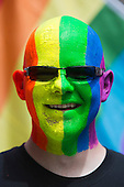 "29 June 2013, London, United Kingdom. Picture: A man whose face is covered in rainbow paint poses in front of a rainbow flag. Pride London 2013 parade starts with the motto ""love (and marriage)""."