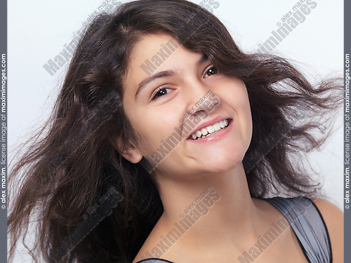 Portrait of a smiling teenage girl with long flying brown hair isolated on white background