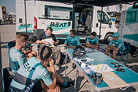"outside (public?) pre-race strategy meeting for the Beat Cycling team<br /> <br /> Antwerp Port Epic 2018 (formerly ""Schaal Sels"")<br /> One Day Race:  Antwerp > Antwerp (207 km; of which 32km are cobbles & 30km is gravel/off-road!)"