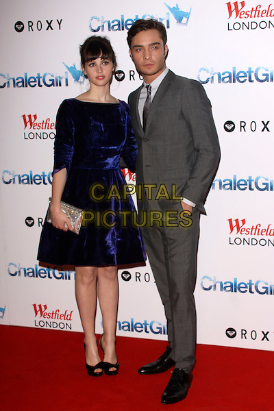 FELICITY JONES & ED WESTWICK.'Chalet Girl' world film premiere at Vue Westfield cinema, Shepherd's Bush, London, England 8th February 2011..full length dress clutch bag blue velvet gold clutch bag grey gray suit tie hand in pocket peep toe platform black shoes .CAP/AH.©Adam Houghton/Capital Pictures.
