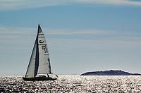 Segelbåt i siluett med solreflexer i bländande vågor i Stockholms skärgård. / Sailing in silhouette with sun glare in dazzling waves in the Stockholm archipelago Sweden.