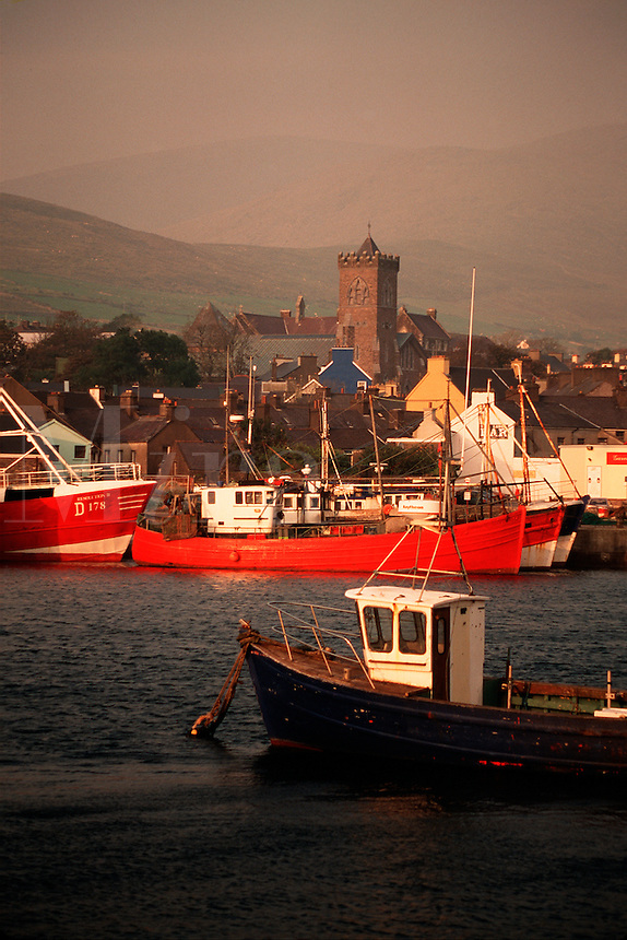 Moody view of Dingle harbor with boats and the city skyline. Dingle, Ireland.