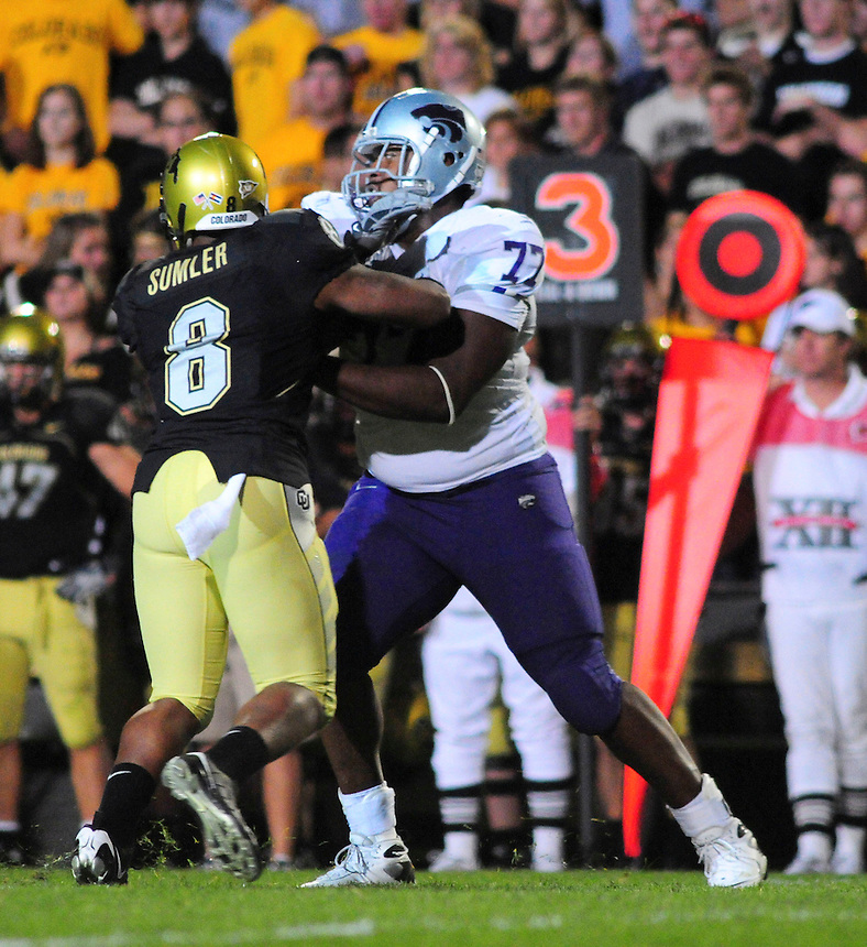 18 October 08: Kansas State tackle Daniel Calvin (77) works against Colorado running back Demetrius Sumler (8). The Colorado Buffaloes defeated the Kansas State Wildcats 14-13 at Folsom Field in Boulder, Colorado.
