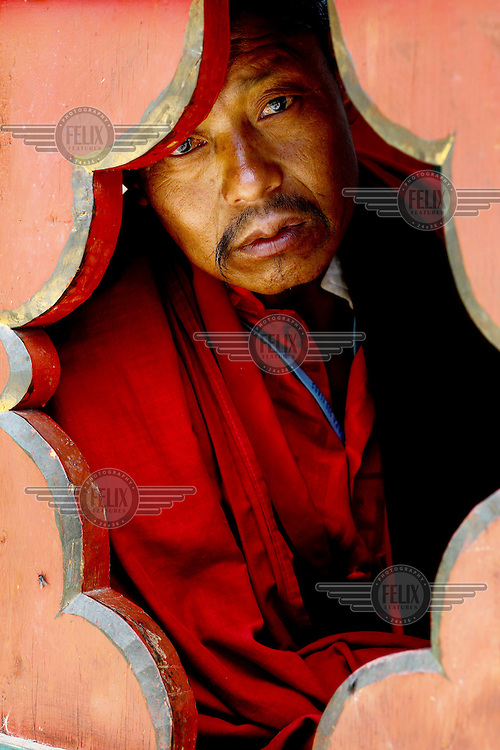 A monk peers through a window at the Taktsang (Dzong) Monastery high up in the Paro Valley.
