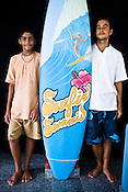 "(Left to right) Satyaraj and Daruka pose with the ""Surfin' Swamis"" surfboard at the Kaliya Mardana Krishna Ashram in the coastal town of Mulki, just north of Mangalore, Karnataka, India.  ..Krishna devotees in the Gaudiya Vaishnava tradition of Hinduism, they are known collectively as the ""surfing swamis."" The ""surfing ashram"" is growing in popularity and surfing here is a form of meditation, a spiritual practice leading to heightened states of awareness."