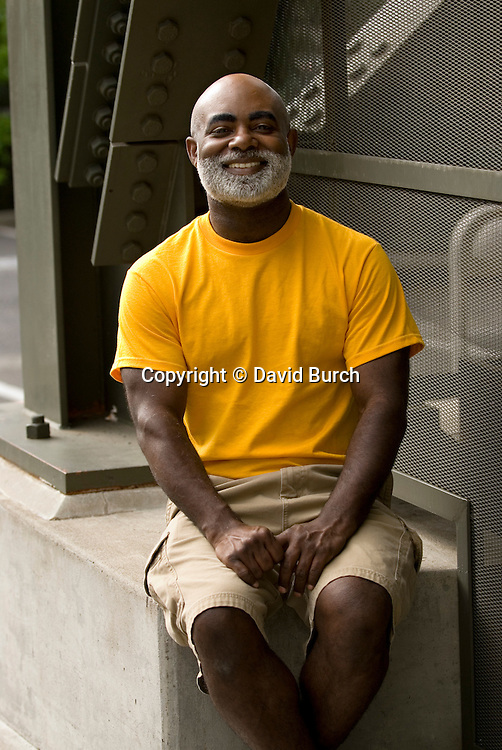 African American man, hands in lap, smiling