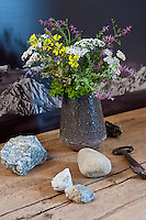 Freshly picked meadow flowers bring a splash of colour to the rough wood work top of the home office in the living room