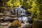 Waterfalls cascade down the boulders in the Mt. Whitney portal, framed by green pines and other vegetation.