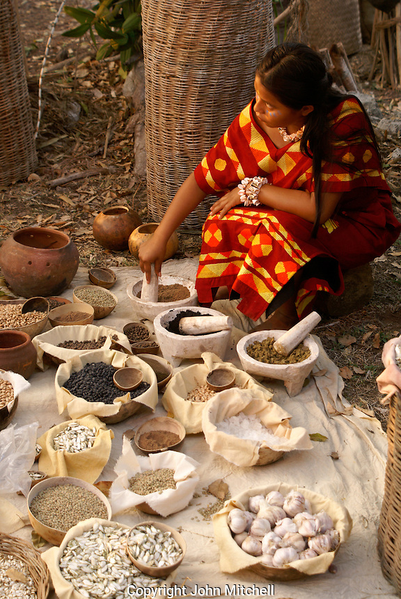 Woman grinding spices and herbs at the recreation of an ancient Mayan market, Sacred Mayan Journey 2011 event, Riviera Maya, Quintana Roo, Mexico