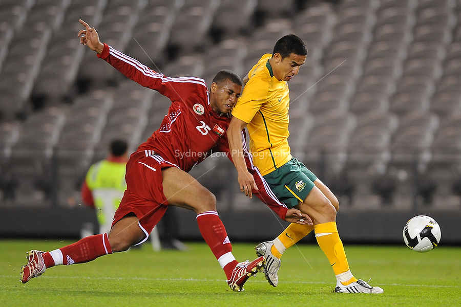 MELBOURNE, AUSTRALIA - OCTOBER 14: Tim Cahill from Australia is tackled by Khalifa Naufli from Oman in a AFC Asian Cup 2011 match between Australia and Oman at Etihad Stadium on October 14, 2009 in Melbourne, Australia. Photo Sydney Low www.syd-low.com