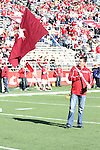 "C.J. McCoy, one of the Washington State University alumni who have waved the Cougar flag on the set of ESPN's College Football ""GameDay"" broadcasts, carries one of the flags out to midfield during a pre-game recognition for all of the Cougar faithful who have treked all over the United States to wave the flag, prior to the Cougars Pac-10 conference contest against the Cal Bears at Martin Stadium in Pullman, Washington, on November 6, 2010."