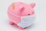 Piggy bank wearing surgical mask, studio shot
