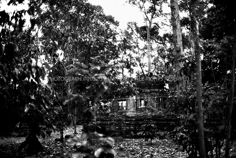 4/20/2003--Angkor Wat Temples, Siem Reap, Cambodia .PHIMEANAKAS : ' Aerial Palace ' .. Phimeanakas is located inside the enclosure of the Royal Palace of Angkor Thom north of Baphuon...Date: Late tenth century-beginning of the 11th century .Kings: Jayavamen V and Udayadityavarman I .Religion: Hindu .Art style: Kleng ..Background .The temple of Phimeanakas is situated near the center of the area enclosed by the walls of the Royal Palace. It must originally have been crowned with a golden pinnacle, as Zhou Daguan described it as the Tower of Gold The temple is built of roughly hewn sandstone blocks and has little decoration. ..According to legend there was a gold tower (Phimeanakas ) inside the royal palace of Angkor the Great where a serpent-spirit with nine heads lived. The spirit appeared to the Khmer king disguised as a woman and the king had to sleep with her every night in the tower before he joined his wives and concubines in another part of the palace. If the king missed even one night it was believed he would die. In this way the royal lineage of the Khmer was perpetuated. ..All photographs ©2003 Stuart Isett.All rights reserved.
