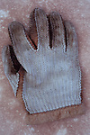 Well-worn and grubby string and leather glove with short cuff used for yachting or golfing lying on antique paper