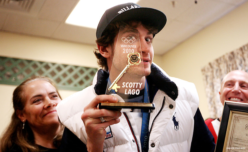 With his parents, Christine Lago, left, and Michael Lago Jr., right, Olympic halfpipe bronze medalist Scotty Lago,facing center, shows off the key to the town of Seabrook he was given during a ceremony at the town hall in Seabrook, N.H., Sunday, Feb. 27, 2010. (Portsmouth Herald Photo/Cheryl Senter)