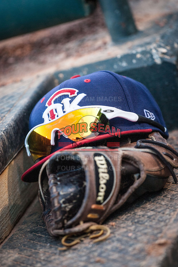 Oklahoma City RedHawks cap and glove sit in the dugout during the Pacific League game against the Colorado Springs Sky Sox at the Chickasaw Bricktown Ballpark on August 3, 2014 in Oklahoma City, Oklahoma.  The RedHawks defeated the Sky Sox 8-1.  (William Purnell/Four Seam Images)