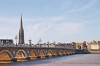 The old bridge Pont de Pierre. Tower and church Eglise Saint Michel. Bordeaux city, Aquitaine, Gironde, France