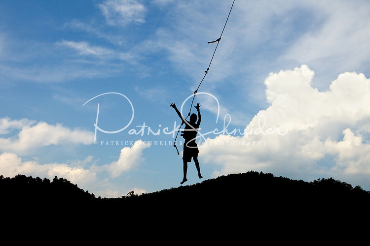 A boy is silhouetted against a partially cloudy sky as he swings on a rope attached to a tree. Photo taken at Watauga Lake in Tennessee.