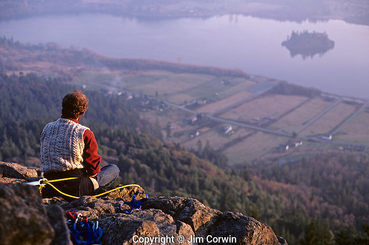 Climber sitting on side of cliff watching the sun go down from Mount Erie from south Fidalgo Island Washington State USA