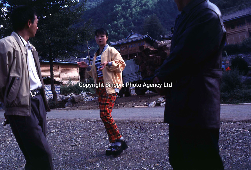 "A prostitute approaches possible clients in a small logging village on the edge of Lugu Lake in Yunnan. The village, a trditional Mosuo village, is being corrupted by tourists, and prostitutes are being shipped in for tourists and truck drivers alike. Women from the Mosuo tribe do not marry, take as many lovers as they wish and have no word for ""father"" or ""husband"". But the arrival of tourism and the sex industry is changing their culture...PHOTO BY SINOPIX"