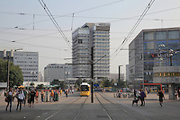 Alexanderplatz, with U-Bahn approaching, people walking, buildings housing shops and offices and the Weltzeituhr or World Clock on the right, Berlin, Germany. Picture by Manuel Cohen
