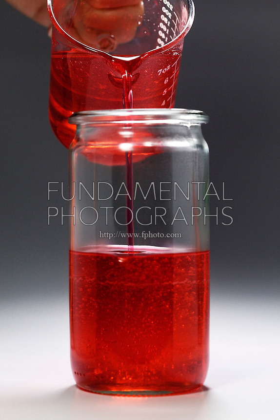 FORMATION OF ROCK CANDY<br /> 1 of 11<br /> Supersaturated Sugar Solution Poured into Beaker<br /> A supersaturated solution of sugar, water, and food coloring is poured into a beaker in preparation for the crystallization of rock candy. The saturation ratio is 3 cups of sugar to 1 cup water.