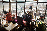 Tibet Buddhist pilgrims look at festival crowds from a 3rd story tea house and restaurant outside the Labrang Monastery during Monlam Festival in Xiahe, Gansu, China.