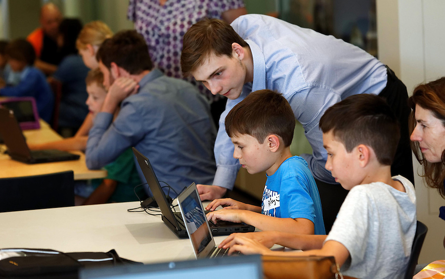 CoderDoJo, a volunteer led coding club for kids where they learn to code. One of the WA chapters is held at Woodsides' Perth HQ. Michael Marshall (19), a computer science intern at Woodside and volunteer mentor with brothers Riley (9) and Tristan (12) Nel of Applecross. photo by Trevor Collens 8/12/2016