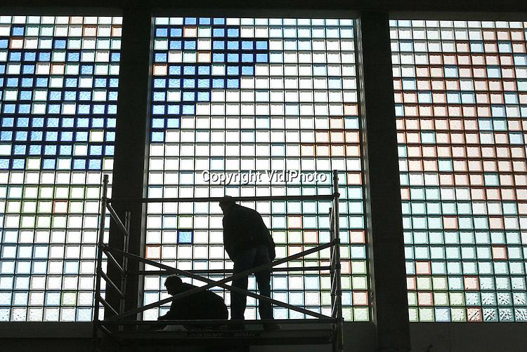 Foto: VidiPhoto..APELDOORN - Bouwvakkers zijn aan het werk met de glazen bouwstenen in het nieuwe kerkgebouw De Hofstad in Apeldoorn-Zuid. De nieuwe kerk in aanbouw van de Samen op Weg-gemeente krijgt bijzondere ramen. Glazen gekleurde stenen vormen een bijbels patroon dat door een kunstenaar is samengesteld. De ramen zijn 3,20 meter breed en 5,50 meter hoog en bestaan uit zestien vlakken. De nieuwe kerk telt 450 zitplaatsen met de mogelijkheid voor uitbreiding, heeft twaalf vergaderzalen en moet maart 2003 klaar zijn. De bouwkosten bedragen 2,22 miljoen euro. Hoofdaannemer is Hufkes uit Apeldoorn en het ontwerp komt van Architectenhuis Apeldoorn.