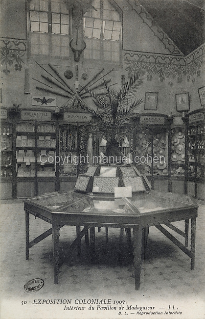 Exhibition in the Madagascar Pavilion, part of the Colonial Exhibition of 1907, held in the Jardin d'Agronomie Tropicale, or Garden of Tropical Agronomy, in the Bois de Vincennes in the 12th arrondissement of Paris, postcard from the nearby Musee de Nogent sur Marne, France. The garden was first established in 1899 to conduct agronomical experiments on plants of French colonies. In 1907 it was the site of the Colonial Exhibition and many pavilions were built or relocated here. The garden has since become neglected and many structures overgrown, damaged or destroyed, with most of the tropical vegetation disappeared. The site is listed as a historic monument. Picture by Manuel Cohen / Musee de Nogent sur Marne