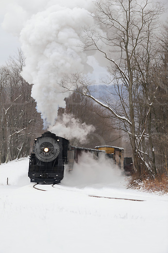 Railroad train rounding a mountain curve making a tall smoke plume in the cold winter air, a vintage steam locomotive pulling hard uphill through the woods with vintage freight cars on the Western Maryland Scenic RR out of Cumberland, Maryland.