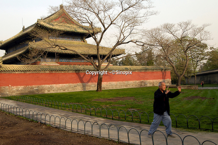 An elderly man does Tai Chi in the morning near the Temple of Heaven in Beijing, China..Dec 2006
