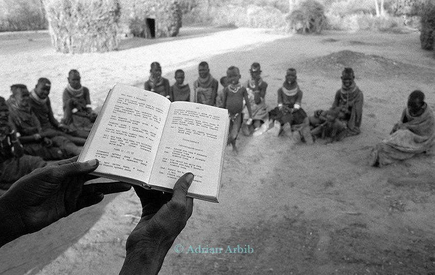 A Turkana village, Kakuma, Northern Kenya.<br /> A lay preacher travels around preaching the bible - seen  here translated in to Turkana - the Turkana god is called Akuj and is simply transformed into God in the Judeo  Christian sense.