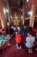 Laos. Luang Prabang. Buddhist worshippers at Wat Xiang Thong.